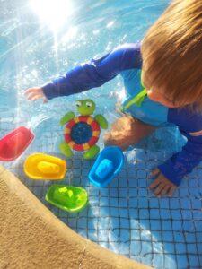 niño en la piscina con barcos y tortuga