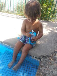 niño con Agua&Fruta en la piscina