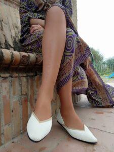 mujer sentada en un banco con las zapatillas de VIVAIA