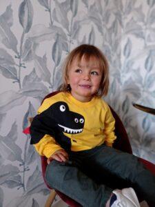 niño sentado en la silla con sudadera de dinosaurio